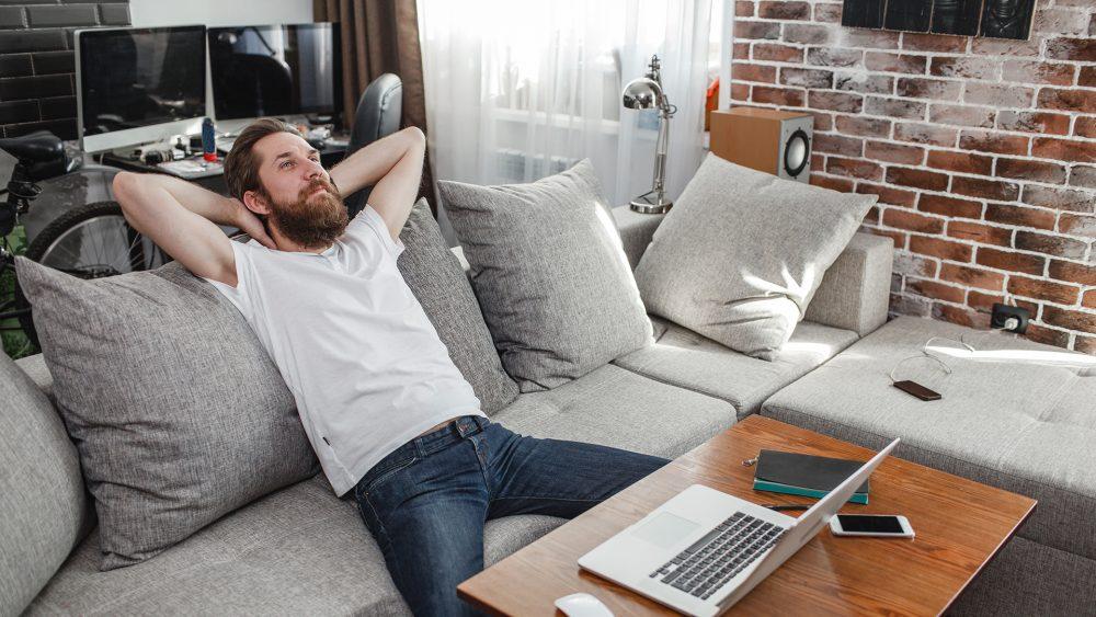 Eine Person sitzt auf einem Sofa. Vor ihr auf dem Tisch ist ein MacBook zu sehen, neben dem Sofa ein Lautsprecher.