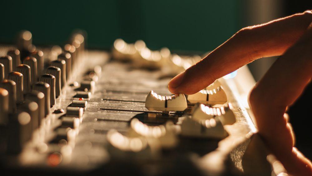 Eine Person bewegt Regler an einem Audio-Mischpult.