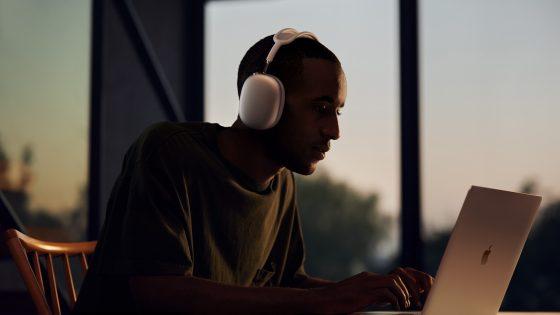 Eine Person mit Apple AirPods Max sitzt vor einem MacBook.