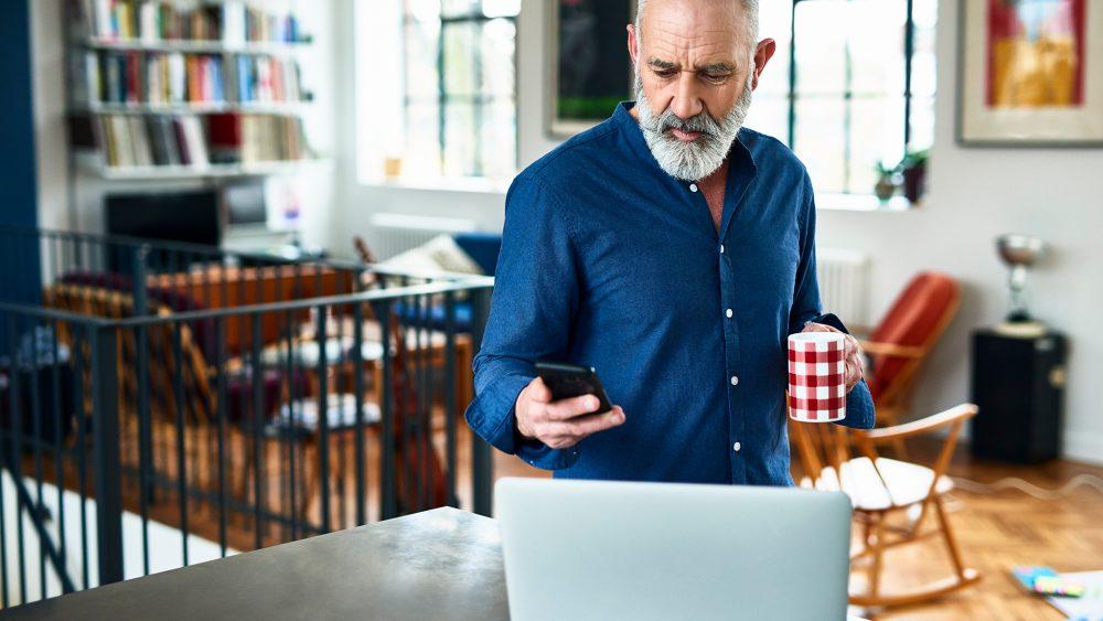 Eine Person steht mit einer Tasse in der Hand vor einem Laptop. In der Hand hält sie ein iPhone.