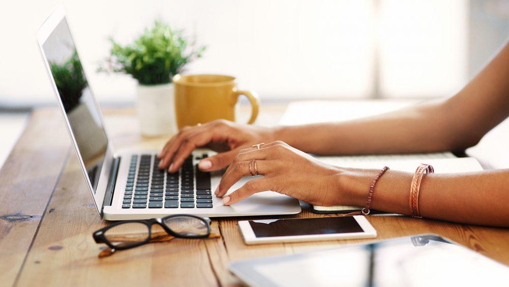 Eine Person tippt auf einem MacBook. Daneben liegen ein Smartphone und ein Tablet.