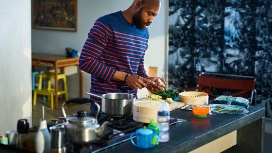 Eine Person steht in der Küche und bereitet Lebensmittel mit einem Dampfgarer zu.