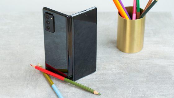 Auf einem Tisch steht ein Galaxy Z Fold 2, daneben eine goldfarbene Dose mit Buntstiften.