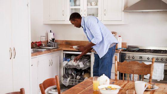 Eine Person räumt nach dem Frühstück Geschirr in eine Spülmaschine.