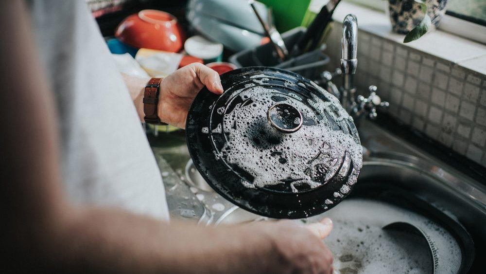 Eine Person hält ein Geschirr-Teil in der Hand, das noch von Schaum bedeckt ist. Im Hintergrund ist weiteres Geschirr in der Spüle zu sehen.