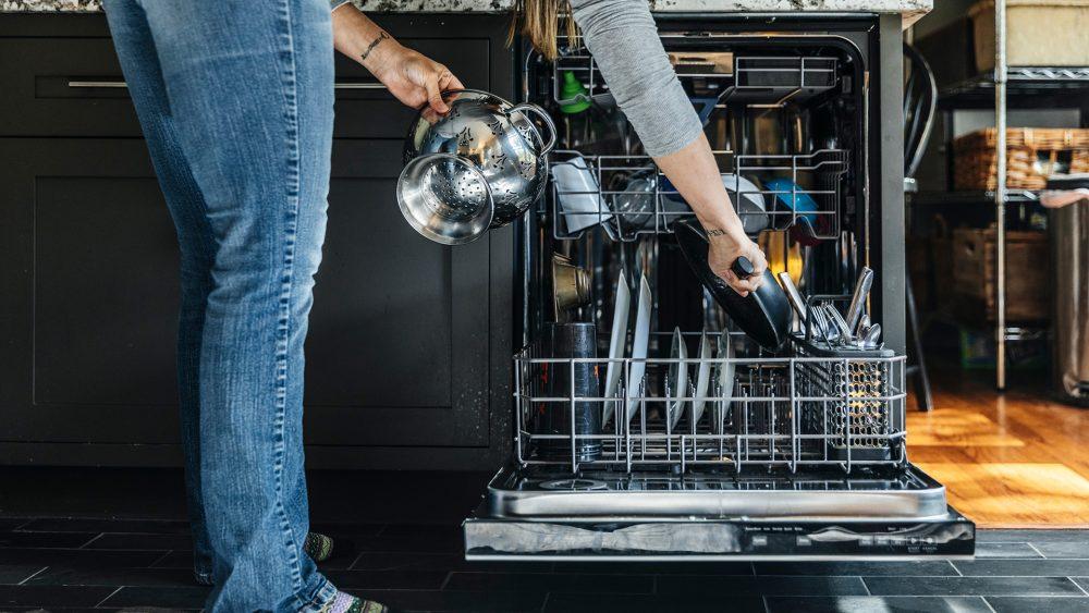 Eine Person räumt eine Pfanne in die bereits gut gefüllte Spülmaschine ein.
