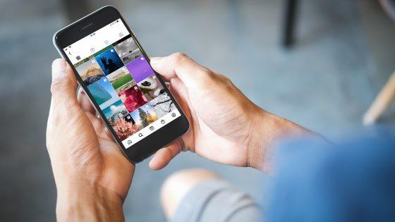 Eine Person hält ein Smartphone in den Händen. Darauf zu sehen ist der Instagram-Feed eines Nutzers.