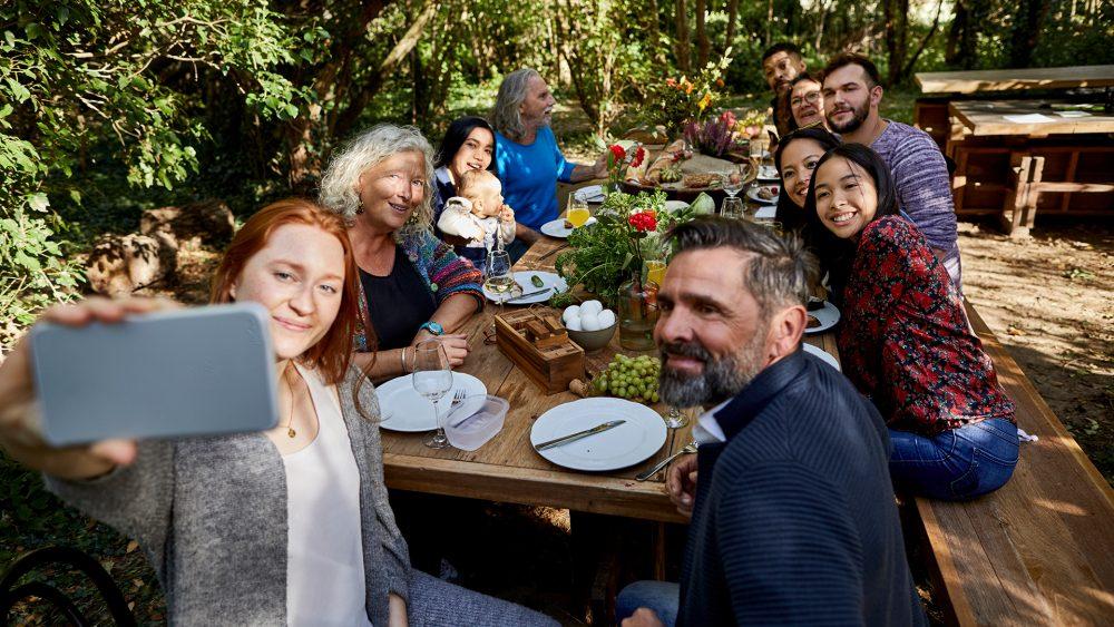 Eine Gruppe Menschen sitzt versammelt an einem Picknick-Tisch im Freien. Die Frau am Kopf des Tisches hält ein Smartphone vor sich, um ein Gruppenselfie zu schießen.