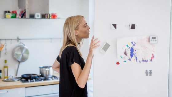 Eine Frau steht in einer Küche und schaut in einen geöffneten Kühlschrank.