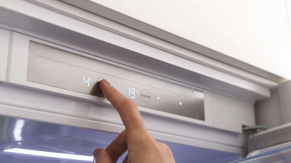 Ein ausgestreckter Zeigfinger tippt auf das Bedienfeld eines geöffneten Kühlschranks, um die Temperatur zu regulieren.