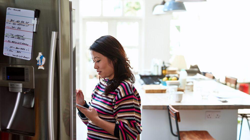 Eine junge Frau steht vor einem geöffneten Kühlschrank. Sie blickt auf das Smartphone in ihrer Hand.