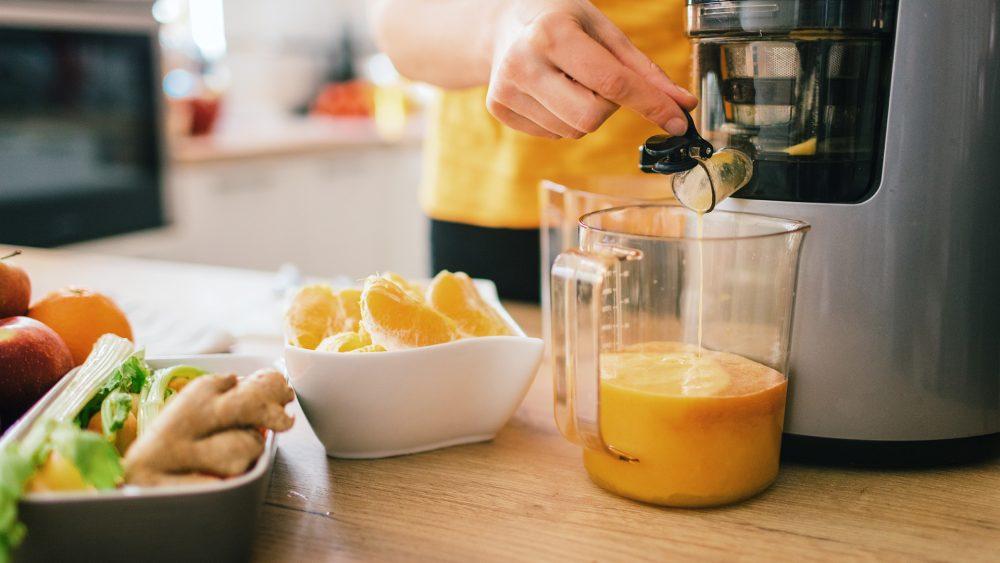 Ein Entsafter und verschiedene frische Lebensmittel stehen auf einer Arbeitsplatte, eine Person bedient den Entsafter.