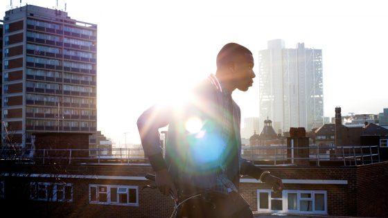 Eine Person lehnt auf einem Fahrrad, das auf einem Hausdach steht. Die Sonne scheint ins Bild und erzeugt einen Lens-Flare-Effekt.