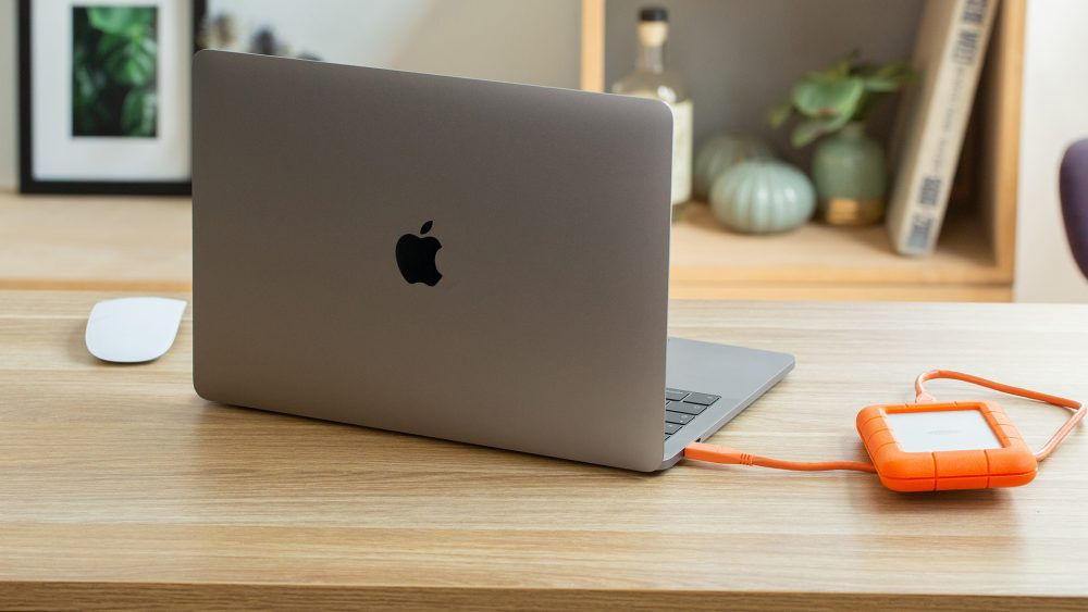 Ein aufgeklapptes MacBook steht auf einem Schreibtisch. Daneben liegt eine angeschlossene, externe Festplatte.