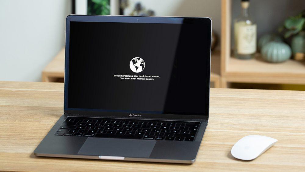 Ein aufgeklapptes MacBook steht auf einem Tisch. Auf dem Display ist ein Hinweis zur Wiederherstellung des Systems zu lesen.