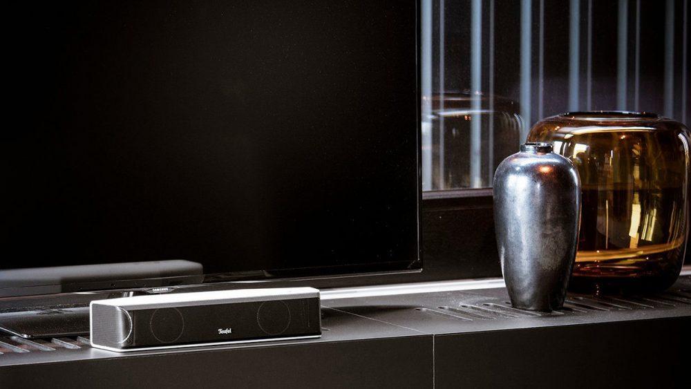 Auf einem Design-Sideboard steht eine Soundbar vor einem Flachbild-TV-Gerät.