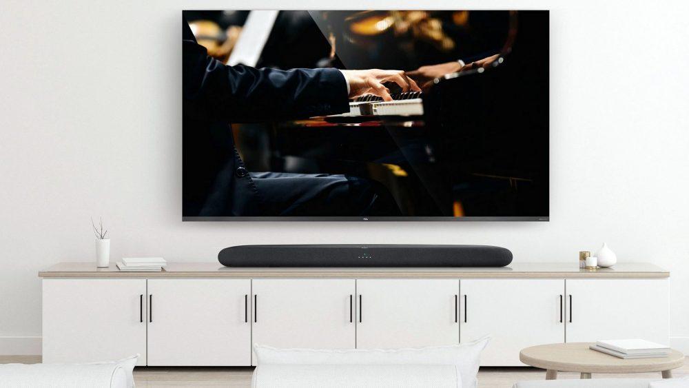 An der Wand über einem TV-Sideboard hängt ein TV-Gerät, auf dem Board steht eine Soundbar.