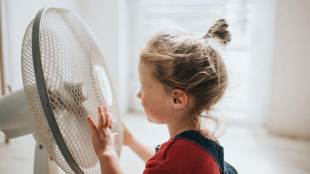 Ein Kind steht vor einem eingeschalteten Ventilator, seine Haare wehen im Wind.