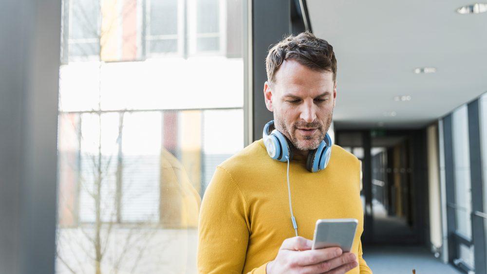 Ein Mann steht in einem Flur eines Bürogebäudes und schaut auf sein Smartphone. Um seinen Hals baumelt ein Paar Kopfhörer.