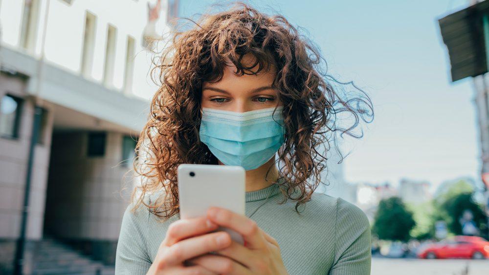 Eine Frau mit Gesichtsmaske schaut auf ihr Smartphone. Sie ist der Kamera zugewandt, das Smartphone selbst ist nur von hinten zu sehen.