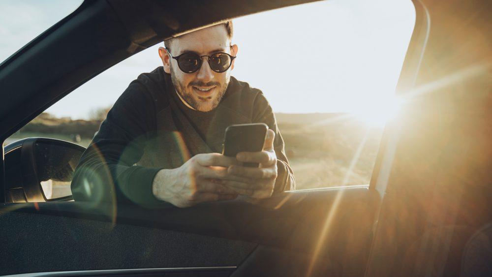 Ein Mann mit Sonnenbrille lehnt sich in ein Fahrzeug. Dabei schaut er auf sein Mobiltelefon.