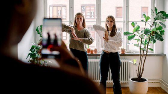 Zwei junge Frauen tanzen eine Choreografie für ein Video. Im Vordergrund ist unscharf ein Smartphone zu erkennen, das die beiden filmt.