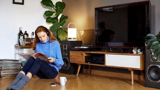 Eine Frau sitzt auf dem Fußboden und liest in einem Magazin, hinter ihr sind ein Sideboard mit TV-Gerät und Lautsprechern rechts und links zu sehen.