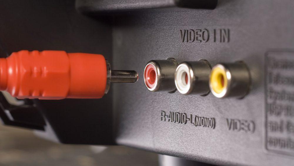 Auf der Rückseite eines TV-Gerätes befindet sich ein Composite-Anschluss mit drei Cinch-Buchsen, ein Cinchstecker befindet sich vor der roten Buchse.
