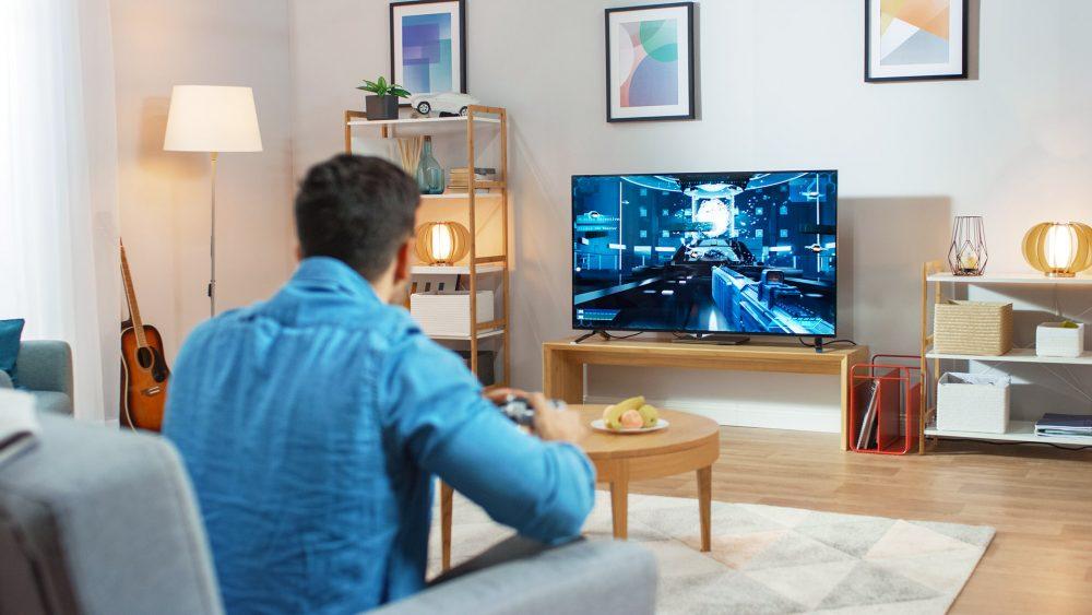 Ein Mann sitzt mit einem Controller auf dem Sofa und spielt ein Spiel auf dem Fernseher.
