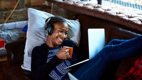 Eine Person liegt auf einem Sofa, hält eine Tasse in der Hand und videotelefoniert über ein Notebook.