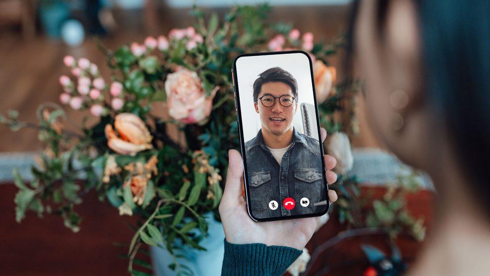 Eine Person schaut in ihr Smartphone. Dort ist eine andere Person zu sehen. Sie kommunizieren per Videotelefonie.