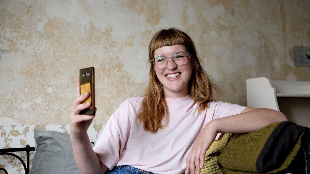 Eine Person lehnt an einem Sofa und telefoniert per Video.