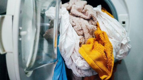 Aus einer Waschmaschine hängen einige Handtücher und Teile von Bettwäsche heraus.