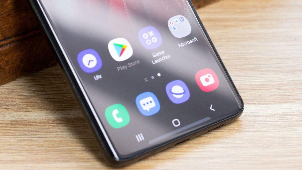 Ein Smartphone lehnt an einem Gegenstand. Im Detail ist auf dem Bildschirm der Google Play Store zu sehen.