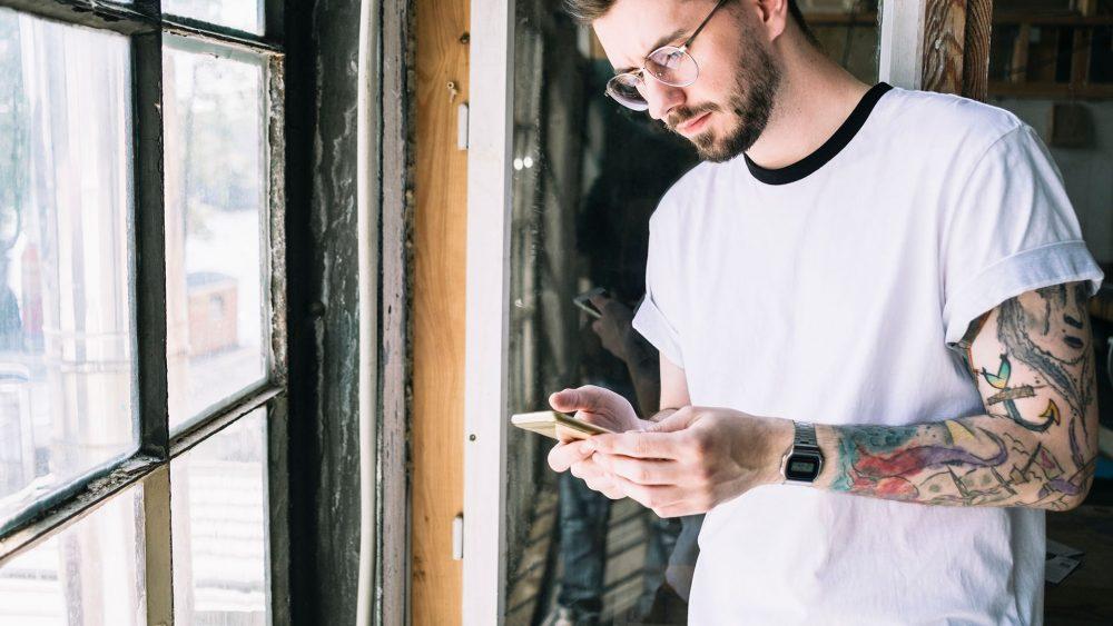 Eine Person steht vor einem Fenster und schaut auf ihr Android-Smartphone.