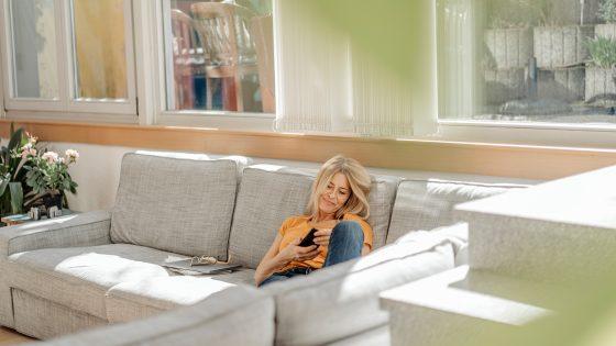 Eine Person sitzt auf einem Sofa. Von draußen scheint die Sonne in den Raum.