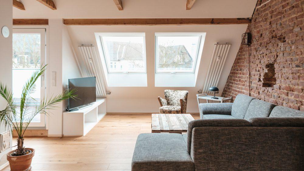 Blick in ein Wohnzimmer im Dachgeschoss eines Hauses mit einem großen Sofa und Dachschrägen.