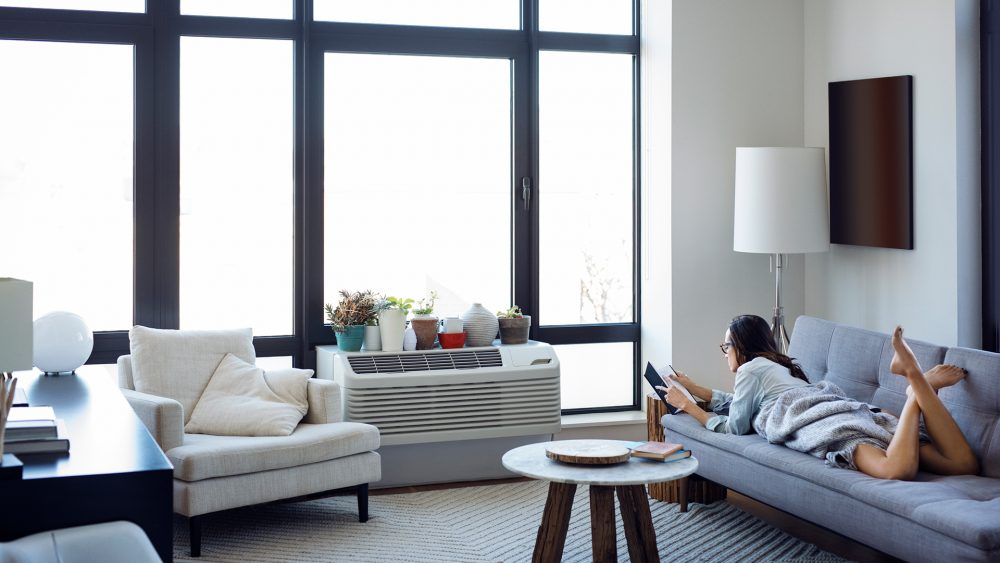 Eine Person liegt auf einem Sofa vor einer großen Fensterfront. Mittig vor den Fenstern ist eine Klimaanlage zu sehen.