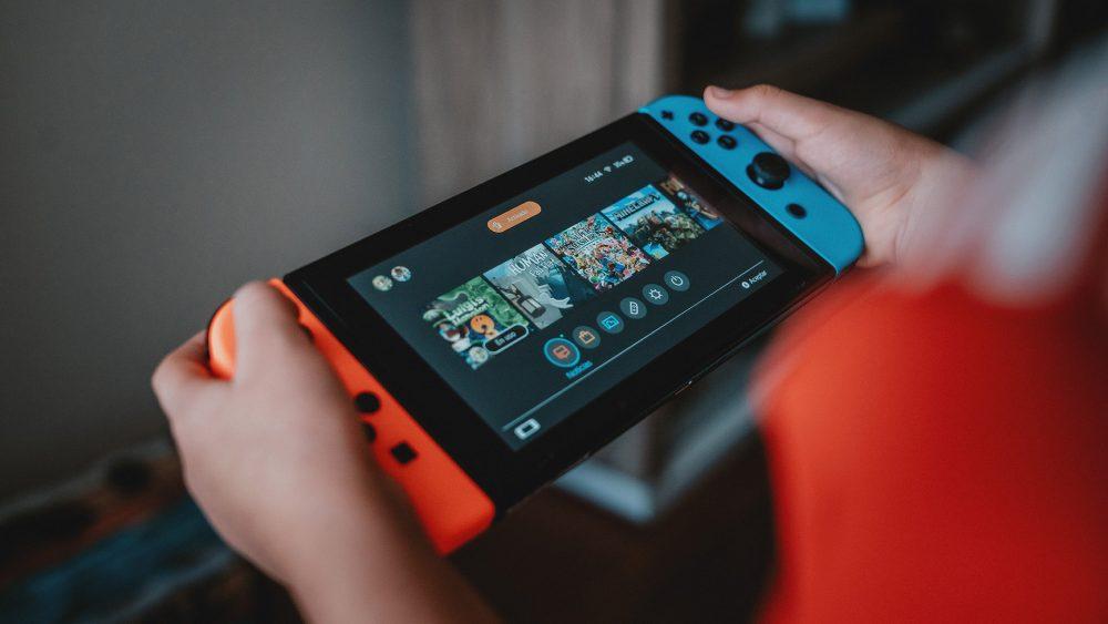Eine Person hält eine Nintendo Switch in der Hand und schaut die Spiele im Hauptmenü an.