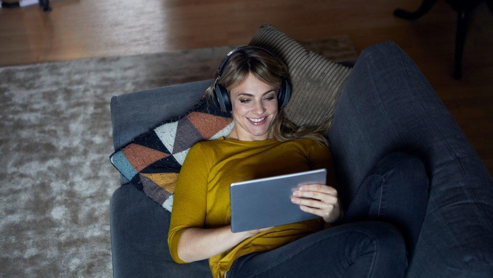 Eine Person liegt auf dem Sofa, trägt Kopfhörer und spielt etwas auf einem Tablet.