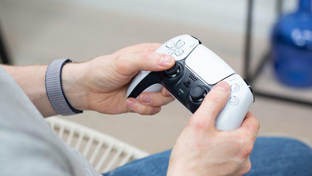 Eine Person hält einen DualSense-Controller der PS5 in Weiß in der Hand.