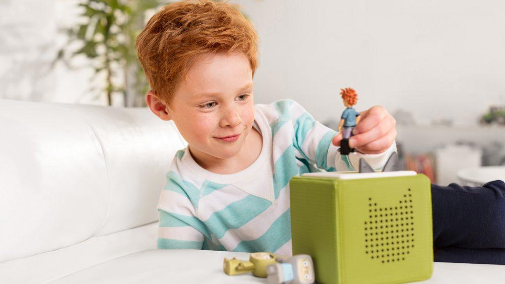 Ein Kind sitzt vor einer Toniebox in grüner Ausführung und stellt gerade eine Figur darauf.