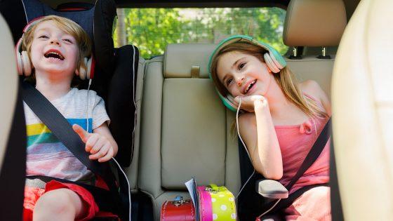 Zwei Kinder mit Kopfhörern auf den Ohren sitzen auf der Rückbank eines Autos