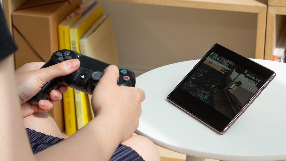 Eine Person hält einen PS4-Controller in der Hand und spielt auf einem Samsung Galaxy Z Fold2 ein Spiel.