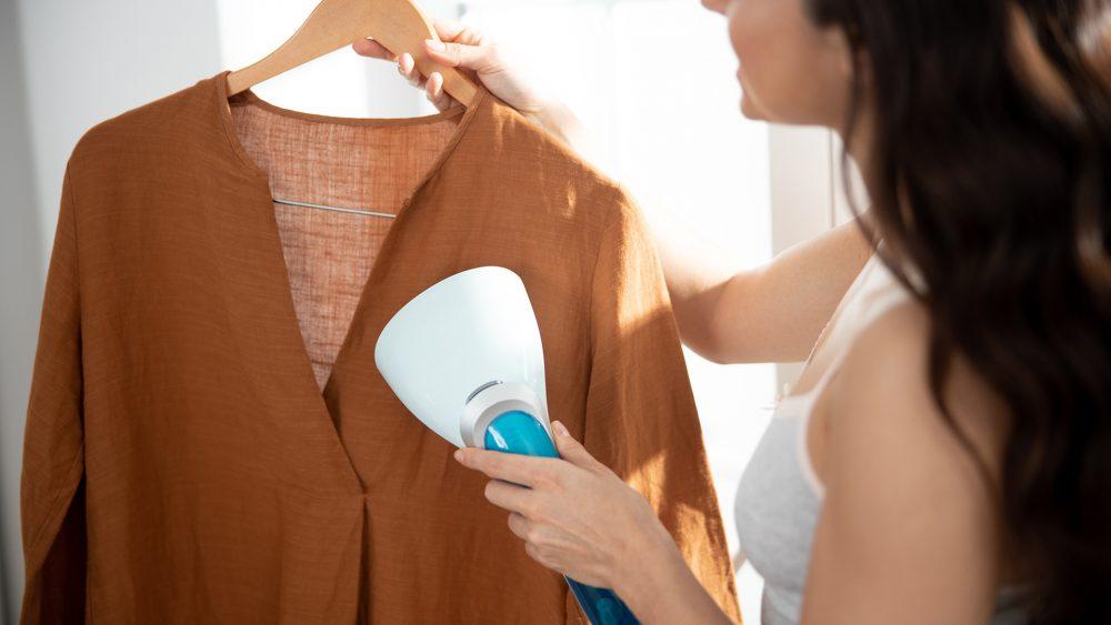 Eine Person hält eine Bluse auf einem Bügel in der einen Hand, in der anderen hält sie eine Dampfbürste.