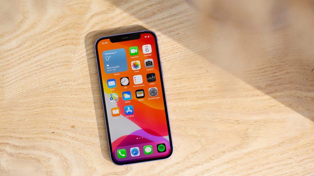 Ein iPhone 12 liegt auf einem Holztisch. Auf dem Display ist der Home-Bildschirm zu sehen.