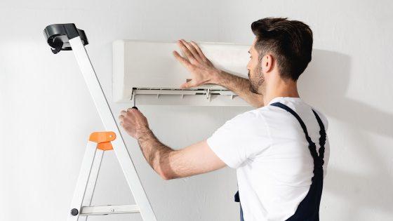 Eine Person auf einer Leiter schraubt die Abdeckung einer Split-Klimaanlage auf.
