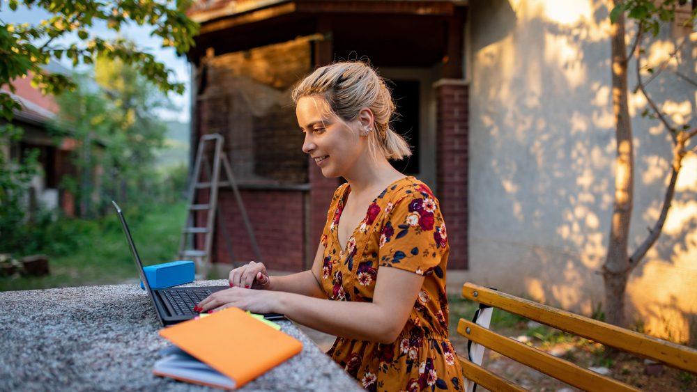 Eine Person sitzt in der Natur und arbeitet auf ihrem Notebook.