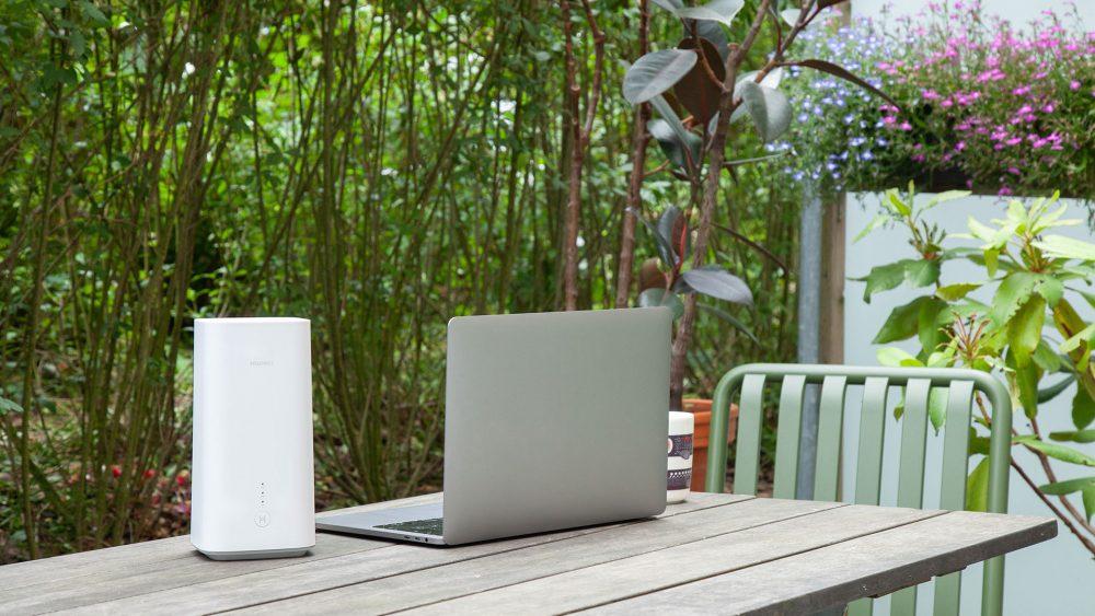 Der Vodafone GigaCube von Huawei auf einem Tisch im Freien. Daneben steht ein Notebook.