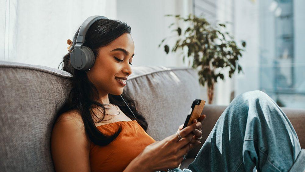 Eine junge Frau sitzt auf dem Sofa, schaut auf ihr Smartphone und hört über einen Kopfhörer Musik.